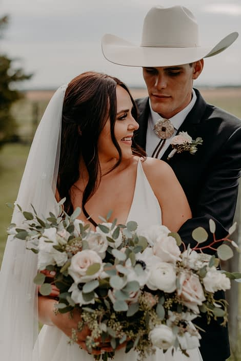 Erika and Colt embracing; groom is wearing a blush and white boutonniere made of roses and eucalyptus; bride is holding a blush, ivory and white bridal bouquet featuring quicksand roses, panda anemones, lisianthus, ranunculus and a mixed variety of eucalyptus greenery.