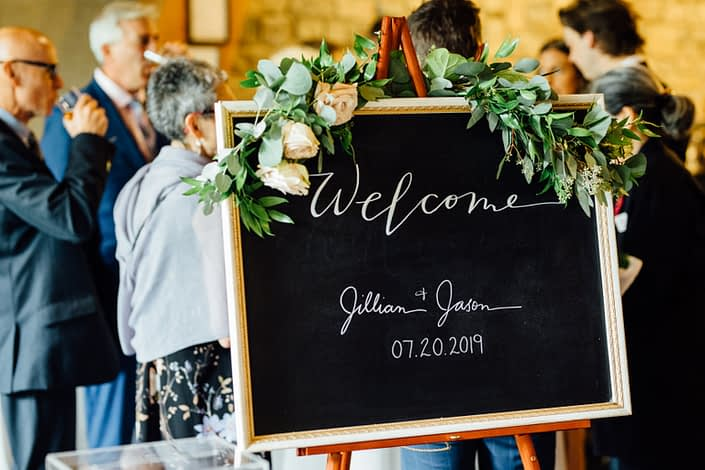 """Jill and Jason's """"Welcome"""" sign decorated with a fresh greenery garland made of eucalyptus and italian ruscus accented by quicksand roses."""