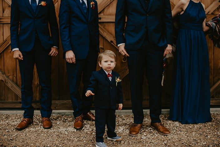 Rustic Fall Wedding ring bearer wearing a magnet boutonniere designed with orange spray roses, hypericum and greenery.