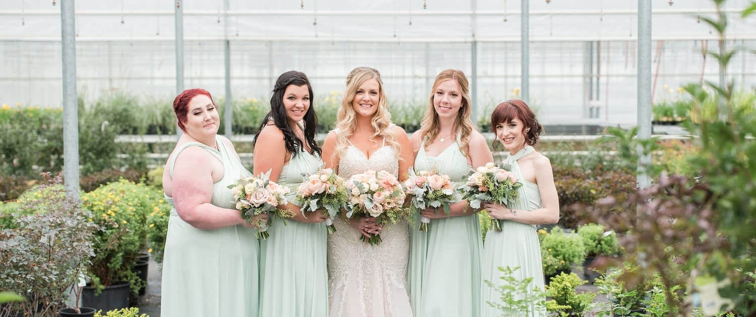 Megan and her bridesmaids carrying blush pink bouquets made of roses, lisianthus, astilbe, dusty miller and eucalyptus greenery.