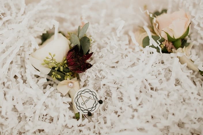 Boutonnieres for Briana and Mark's Glam Jewel Tone Wedding designed with white spray roses, burgundy astrantia and eucalyptus greenery.