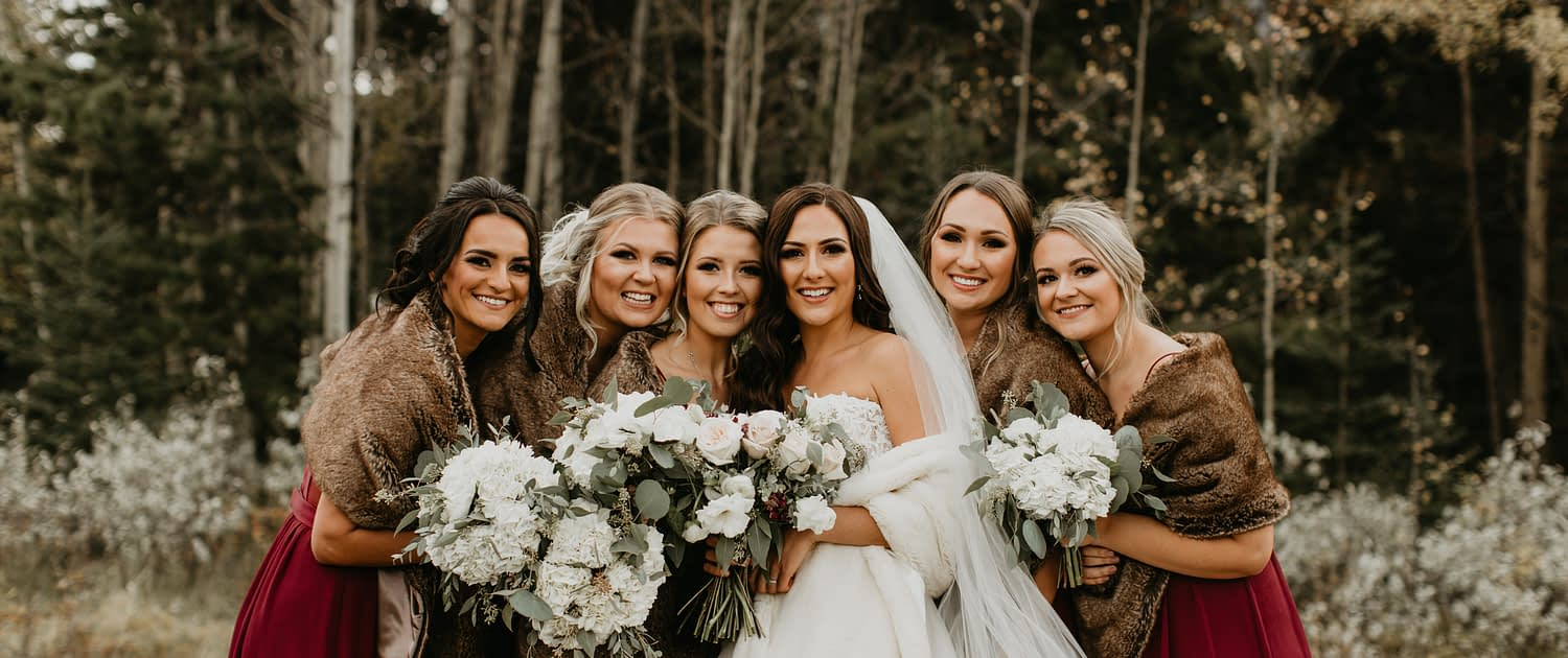 Brittany and her bridesmaids; elegant Canmore Wedding; bridesmaids wearing burgundy dresses and brown fur shawls carrying white hydrangea bouquets; bride wearing white gown and veil with white fur shawl and carrying blush and ivory bouquet featuring quicksand roses, white o'hara garden roses, lisianthus, ranunculus, astrantia and eucalyptus