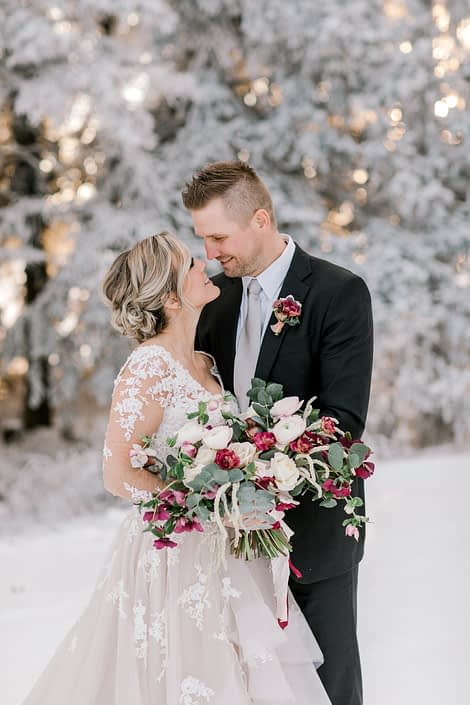 Bride and groom looking at one another with blush and burgundy bouquet and boutonniere