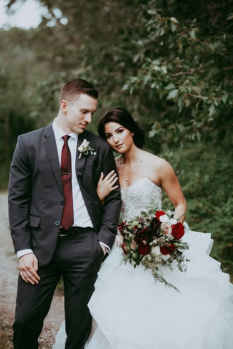 Bride and groom with boutonniere and bouquet featuring burgundy and mauve flowers including roses and dahlias with eucalyptus and plumosa greenery