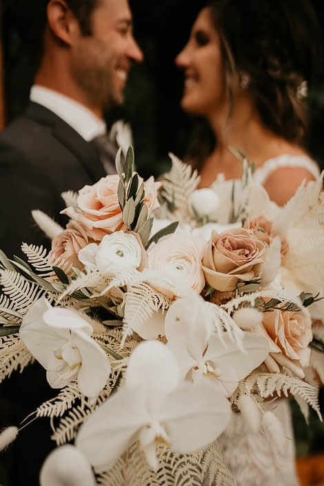 blush and white rustic bridal bouquet designed with roses, ranunculus, orchids, bunny tail, astilbe, bleached bracken fern and olive branches