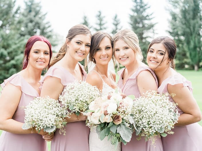 Bride, Taryn, surrounded by her bridesmaids; bride is wearing a white lace bridal gown and holding a dusty rose bouquet featuring rose gold painted scabiosa pods, white o'hara garden roses, quicksand and amnesia roses, ranunculus, astilbe, babies breath, dusty miller and eucalyptus greenery; bridesmaids are wearing elegant rustic dusty pink dresses and carrying babies breath bouquets.
