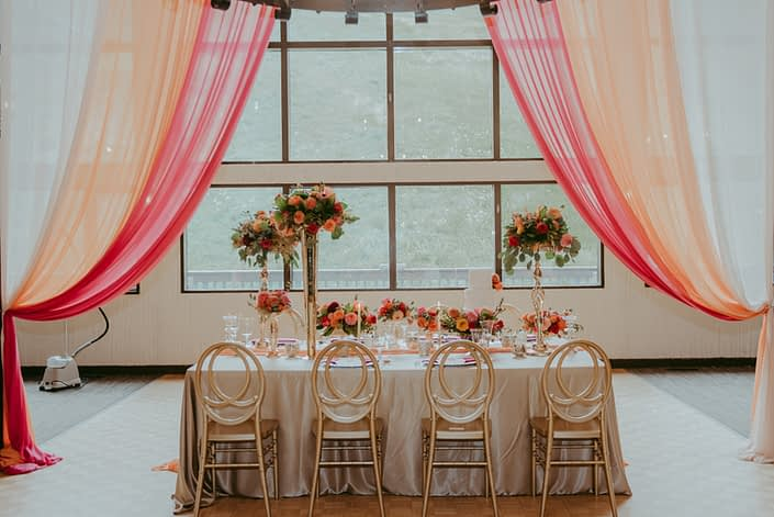 Fuchsia, orange and gold table display with high and low flower arrangements