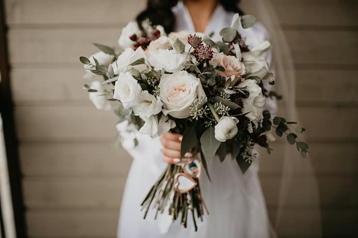 Brittany's bridal bouquet designed with white o'hara garden roses, quicksand roses, white ranunculus, white lisianthus, burgundy astrantia and eucalyptus greenery with rose gold photo locket