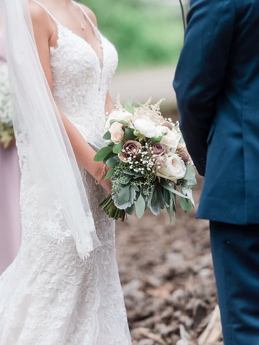 Bride wearing a lace gown and holding a dusty rose bridal bouquet featuring rose gold painted scabiosa pods, white o'hara garden roses, quicksand roses, amnesia roses, babies breath, astilbe, ranunculus, dusty miller and eucalyptus.