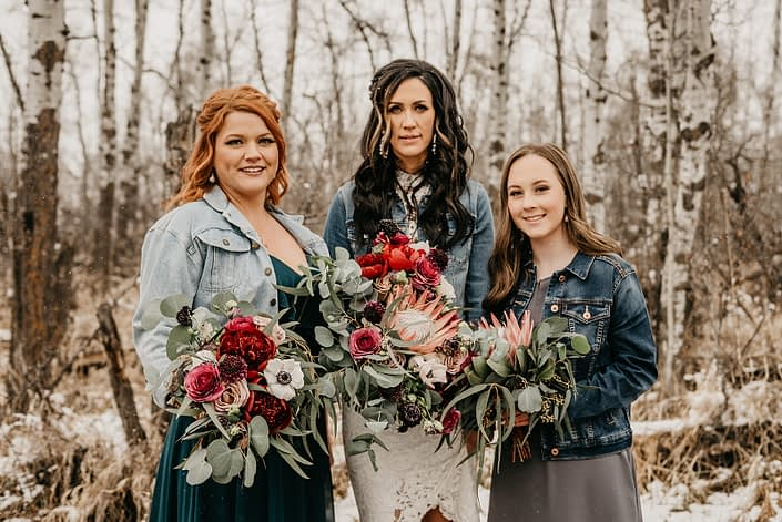 Rustic Boho Chic Wedding - Bride holding bridal bouquet made of king protea, red peonies, pink roses, plum scabiosa, panda anenome, and eucalyptus greenery. She is standing next to her bridesmaid who is holding a bouquet made of red peony, blush and pink roses, and eucalyptus greenery. On her other side is her flower girl who is holding a bouquet made of single king protea and eucalyptus greenery. The bride, bridesmaid and flower girl are all wearing jean jackets.