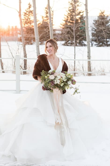 Winter bride with brown fur shawl and bridal bouquet with blush ranunculus and ivory roses