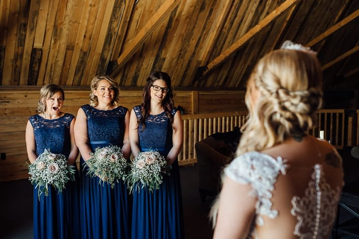 Kelsie's Bridesmaids wearing dark blue dresses and holding bouquets featuring quicksand roses and gypsophila with a variety of eucalyptus greenery.
