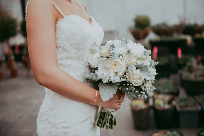 bride holding a bouquet of white peonies, ivory roses and pale blue delphinium with babies breath