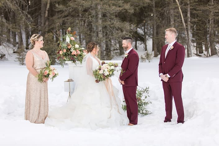 Winter wedding party with bridesmaids in blush sequin and groomsmen in burgundy suits holding flowers in brugundy, blush and ivory in front of a white mantle