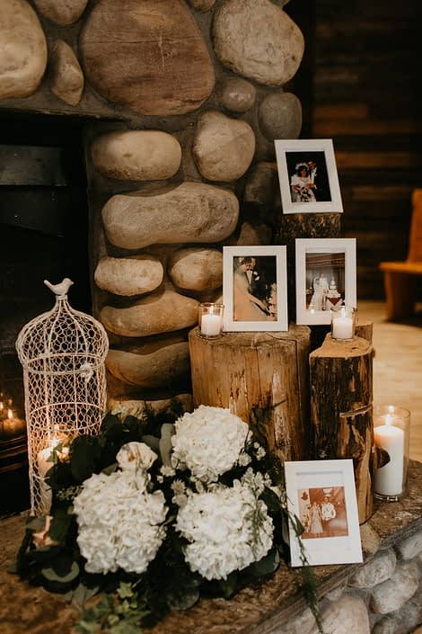 Photo memorial with tree stumps, white bird cage, candles and white hydrangea arrangement