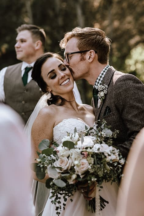 bride and groom with bouquet of white and blush roses and eucalyptus greenery