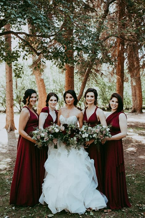 Rikki Lee's burgundy bridal party carrying bouquets designed with dahlias, garden roses, roses, lisianthus, plumosa and eucalyptus
