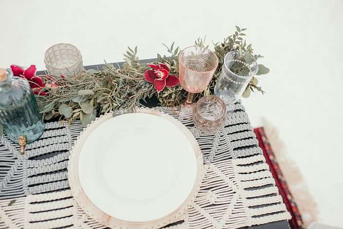 tp view of sweetheart table in a winter photoshoot with fresh eucalyptus greenery garland and burgundy orchids