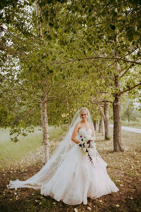 Bride in white veil in the summer trees with cascade orchid and lily bridal bouquet