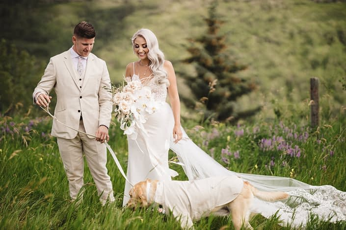 Bride and groom, Sandra and Brandon, with dog in a suit and boho glam bridal bouquet featuring phalenopsis orchids, quicksand roses, pampas grass, olive branches and eucalyptus greenery.