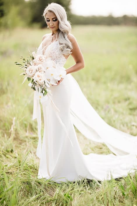 Bride, Sandra, holding her boho glam cascading bridal bouquet designed with quicksand roses, phalenopsis orchids, pampas grass, olive branches and silver dollar eucalyptus.