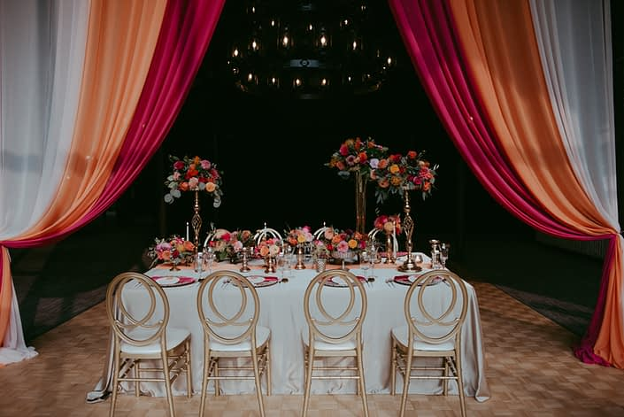 Bold Fuchsia and Orange table with drapery, tall arrangements, compote arrangements with accents of gold