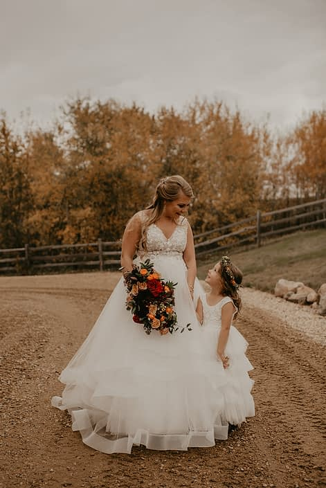 Rustic fall wedding bride and flower girl with orange, red and yellow bridal bouquet and flower crown.