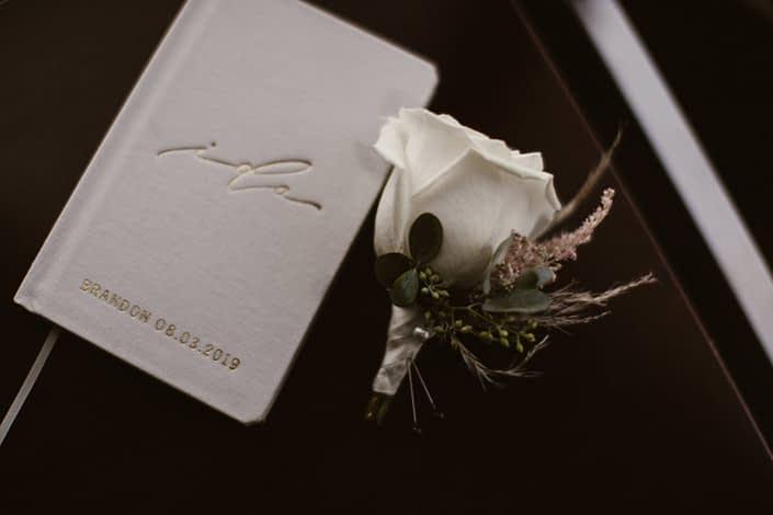 Brandon's white rose boutonniere accented by pale pink astilbe and pampas grass with book of vows.