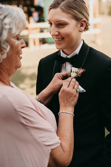 grandmother pinning on boutonniere to bride wearing tuxedo