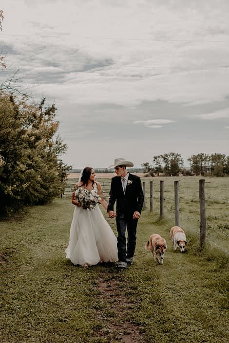 Erika and Colt's Blush and Mauve Country Wedding - bride and groom are walking hand in hand with two dogs and Erika is holding a blush, white and ivory bridal bouquet.