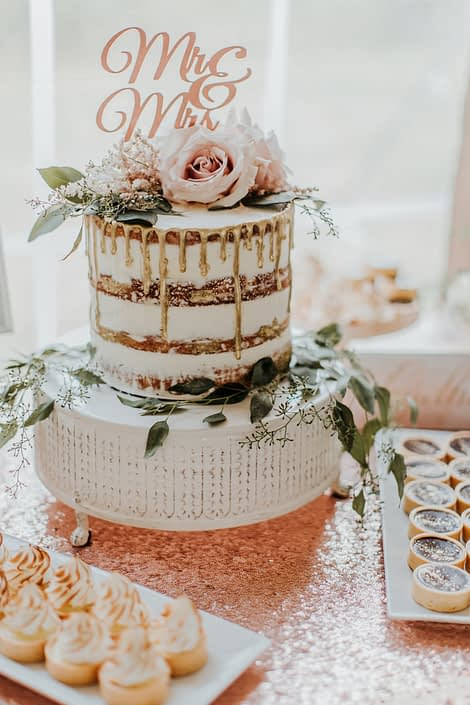 naked cake with gold drip and eucalyptus and blush rose topper and mr and mrs topper on rose gold sequin tablecloth