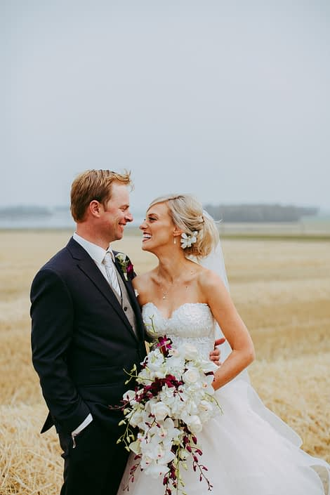 bride and groom in an alberta summer wheat field wedding holding a bridal bouquet designed with white orchids and calla lilies