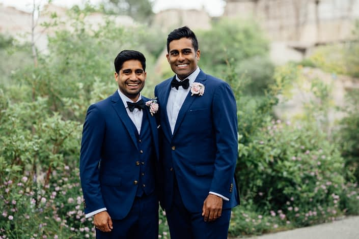 Groom and best man wearing navy suits and blush pink boutonnieres made with spray roses and eucalyptus.