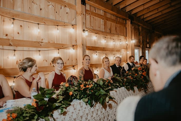 Simple rustic fall wedding head table covered in a garland made of hearts garden roses, burgundy dahlias, golden mustard yellow roses, orange spray roses and salal.