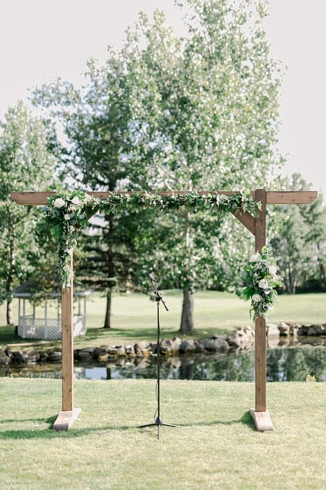 Simple outdoor ceremony archway covered with fresh greenery and white flowers.