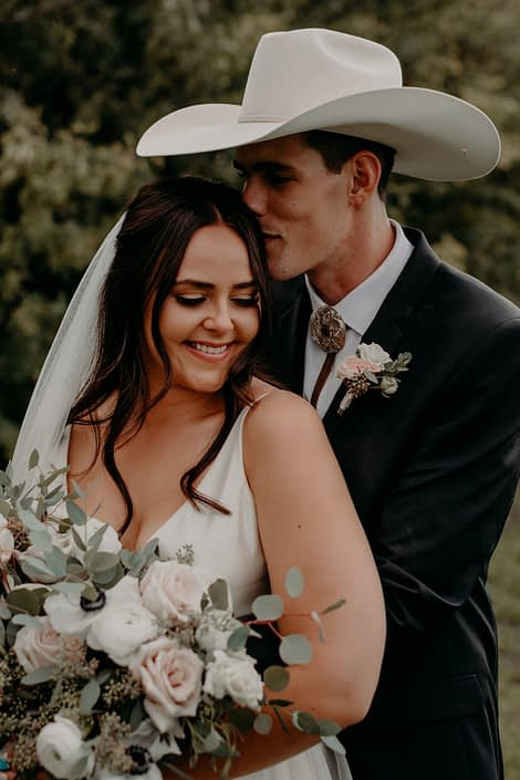 Colt kissing Erika. The groom is wearing a blush and white boutonniere made of spray roses and eucalyptus. The bride is holding a blush, ivory and white bouquet featuring quicksand roses, ranunculus, panda anemones, and lisianthus with a mixed variety of eucalyptus greenery.