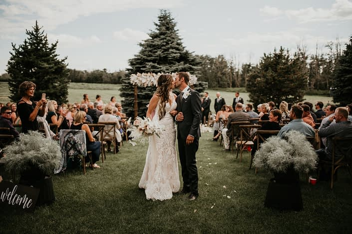 Bride and groom walking down aisle with rustic boho bridal bouquet and boho archway in background