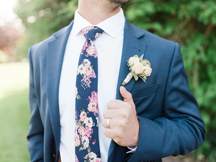 Bride wearing navy and a rose gold boutonniere.