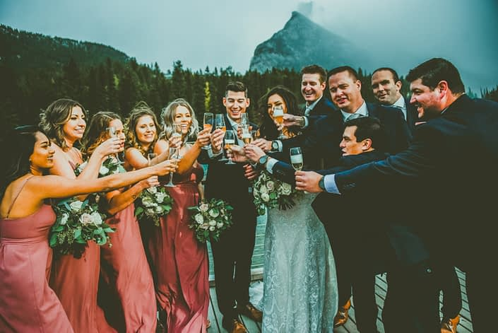 Meagan and Dwayne's bridal party toasting with champagne. Blush and Mauve Canmore Wedding