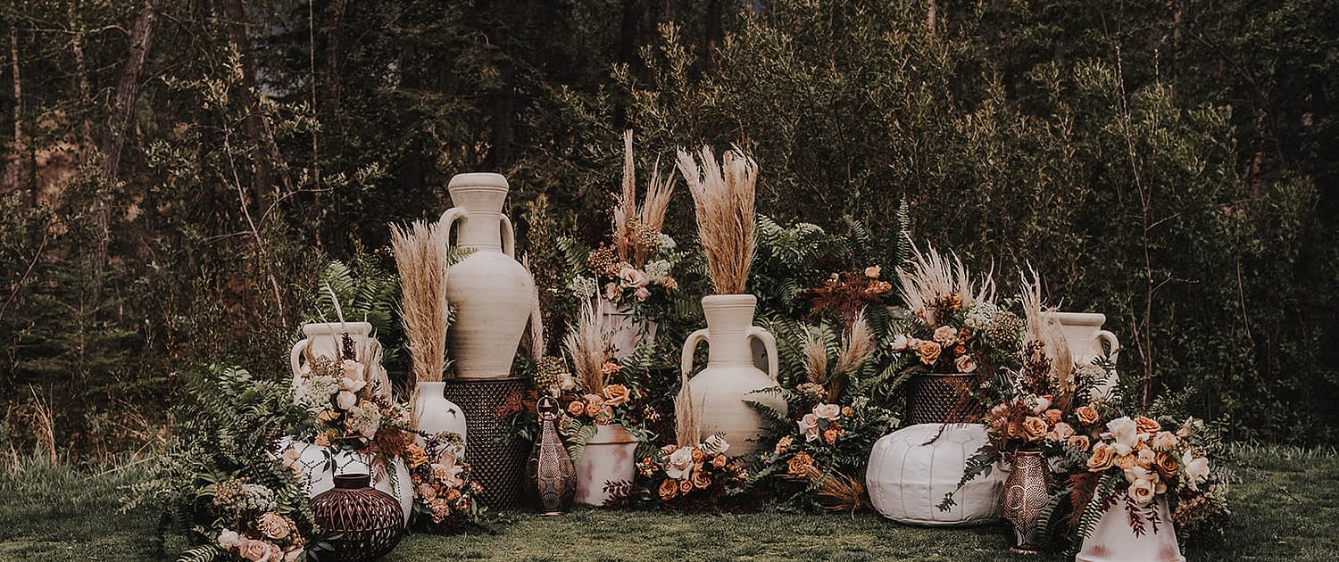 Modern Boho Ceremony set up featuring pampas grass, roses, ferns, and various types of modern boho decor and pottery