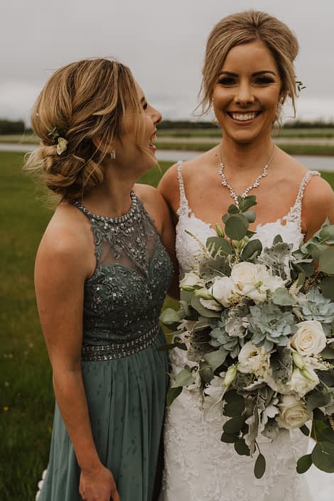 Bride wearing white lace dress and holding a vintage inspired white and grey green bridal bouquet featuring playa blanca roses, lisianthus, astilbe, Blue Star succulents, dusty miller and eucalyptus; bridesmaid wearing grey green bridesmaid dress with white hair flowers.