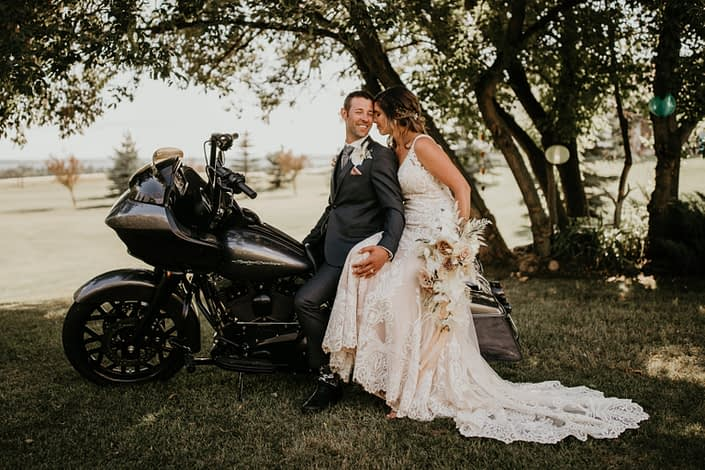 Bride and groom on a motorcycle with bridal bouquet featuring roses, ranunculus, phalenopsis orchids, bunny tail, bleached bracken fern, astilbe, olive branches and eucalyptus