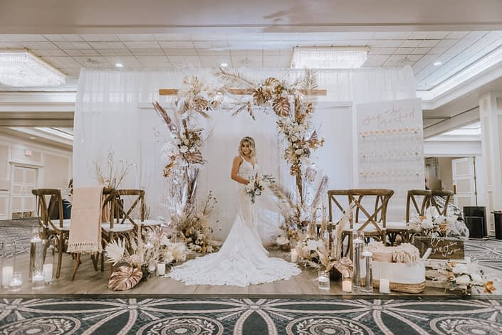 Down the Aisle Wedding Show booth decorated with gold painted monstera leaves, painted sago palm, pampas grass, white and pale pink roses, and other dried leaves and branches. Model wearing lace bridal gown and holding a blush and white bridal bouquet.