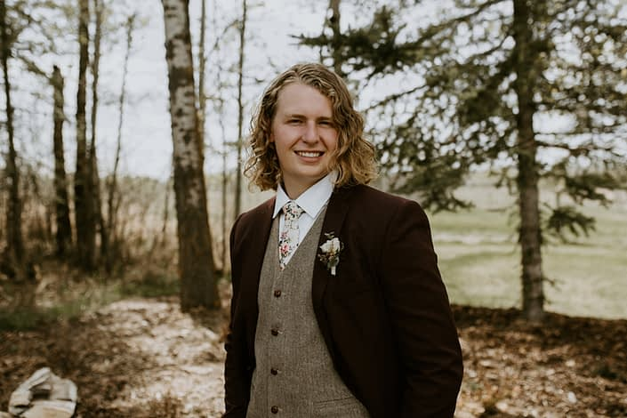 Groom wearing vintage rustic styled suit with a boutonniere designed with astilbe, astrantia and white spray roses