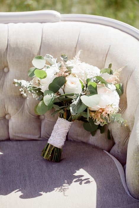 Cream and Blush Vintage Chic Bridal Bouquet on an antique linen tufted sofa; bouquet is made of white o'hara garden roses, quicksand roses, pale pink astilbe, babies breath, white peonies, dusty miller and eucalyptus wrapped with a blush satin and ivory lace overlay.