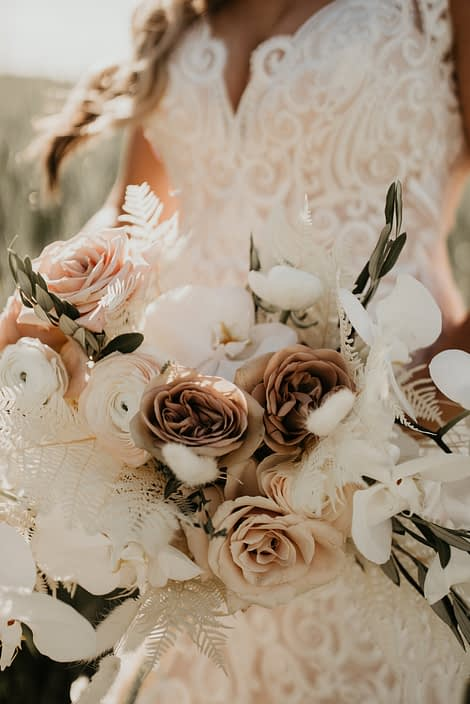 Rustic Boho Bridal bouquet flowers up close; roses, ranunculus, orchids, bunny tail, olive branches, bleached bracken fern