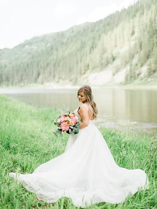 Bride Taylor wearing a white bridal gown and holding a coral charm peony bouquet with golden mustard , quicksand and cappuccino roses, monstera leaves, boston fern and eucalyptus greenery.