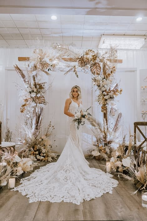 Model holding a white and blush bouquet made of roses and eucalyptus standing under a wooden arch and surrounded by arrangements made of gold painted monstera leaves, sago palm, pampas grass, and other flowers and dried leaves and branches.