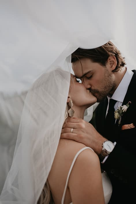 Bride and groom kissing under veil with groom's boutonniere designed with white spray roses