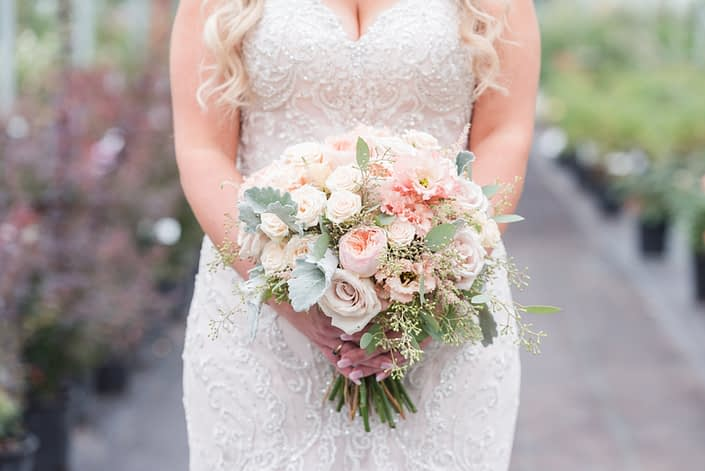 Megan's bridal bouquet made of Juliet garden roses, apricot lisianthus, quicksand roses, Jana spray roses, light blush pink astilbe, and grey toned greenery such as dusty miller and eucalyptus.
